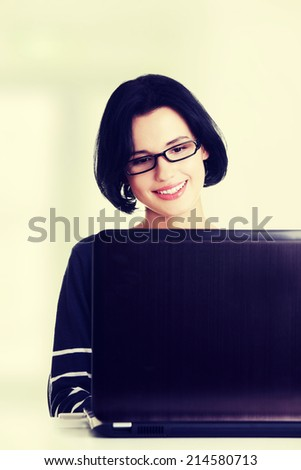 Happy young woman using her laptop, isolated on white. - stock photo