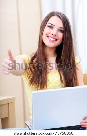 Happy young woman using laptop at home and giving thumb-up gesture to you - stock photo