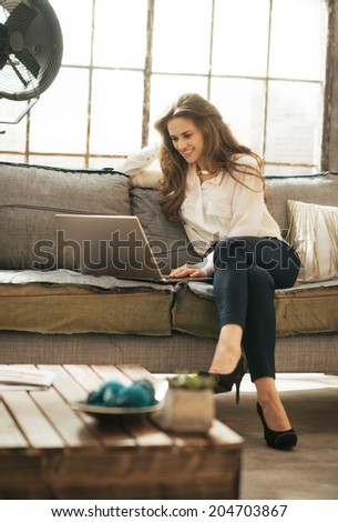 Happy young woman using laptop in loft apartment - stock photo