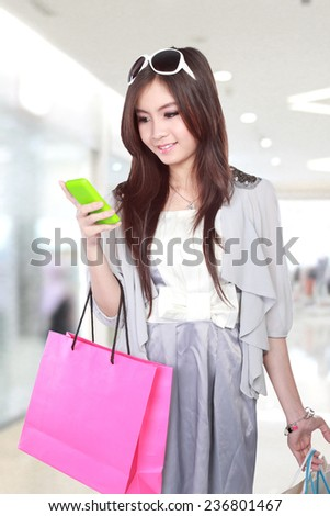 Happy young woman using mobile phone during going shopping in the mall - stock photo