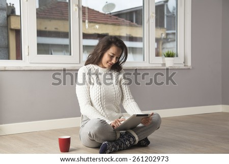 Happy young woman using the tablet computer while sitting on the floor at home. - stock photo