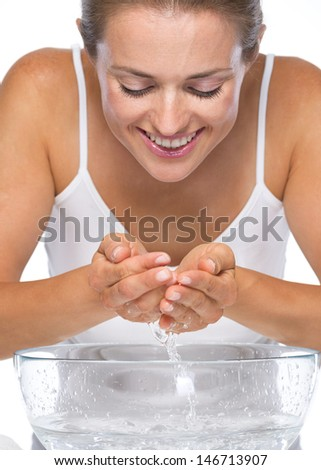 Happy young woman washes face in glass bowl with water - stock photo