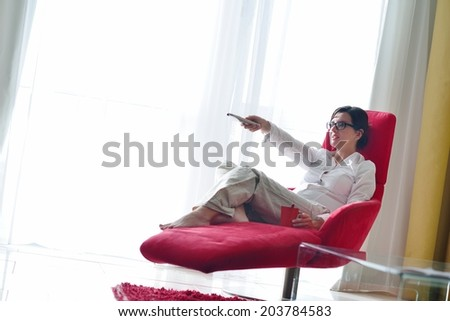 happy young woman watching tv at modern home livingroom - stock photo