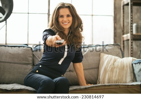 Happy young woman watching tv in loft apartment - stock photo