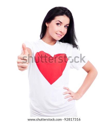 happy young  woman wearing a T-shirt with a big red heart with  thumb up, isolated against white background - stock photo