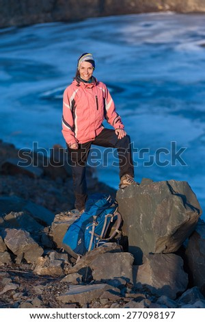 Happy young woman with a backpack smiles at the lake - stock photo
