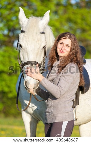 Happy young woman with a horse. - stock photo