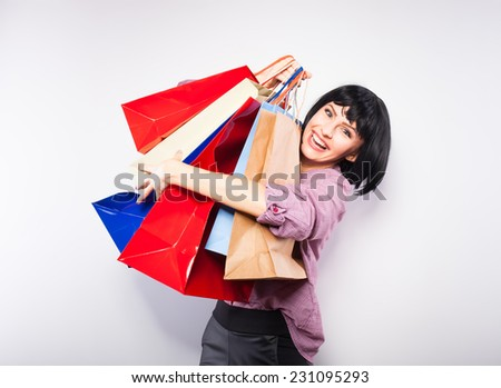 happy young woman with a lot of shopping bags in her arms - stock photo