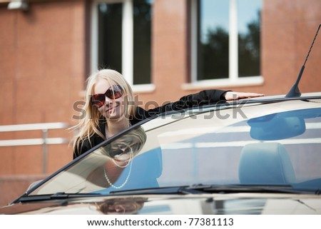 Happy young woman with a new convertible - stock photo