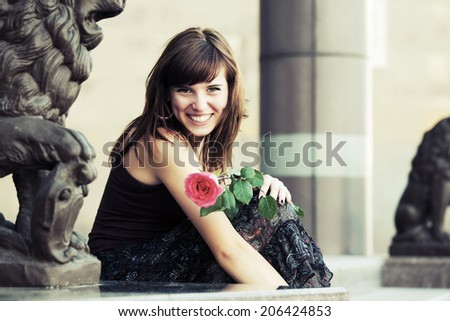 Happy young woman with a red rose - stock photo
