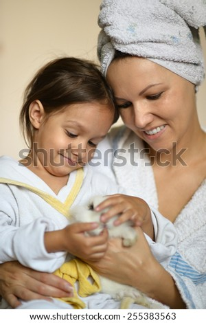 happy young woman with a young daughter and a rabbit - stock photo