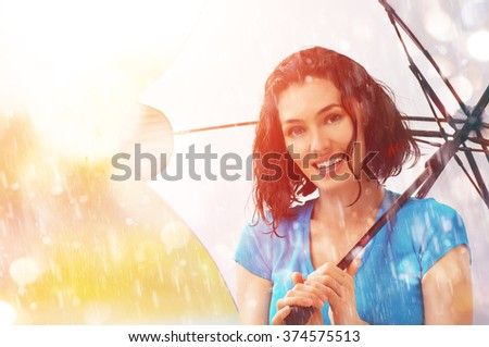 happy young woman with an umbrella in the rain on nature - stock photo