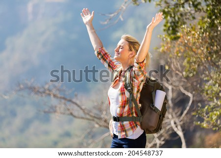 happy young woman with arms open on top of the mountain - stock photo