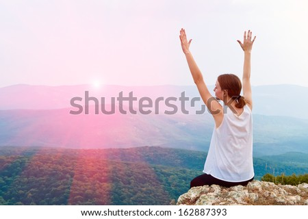 Happy young woman with arms raised. Girl sitting on a cliff side.  - stock photo