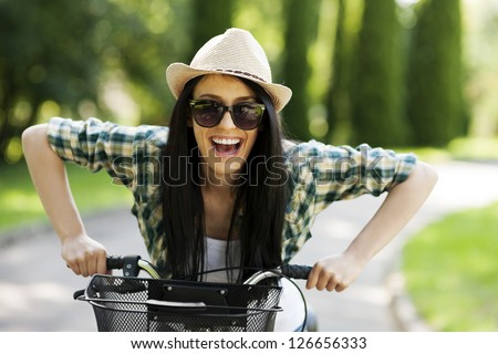 Happy young woman with bicycle - stock photo