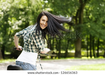 Happy young woman with bike in the park - stock photo