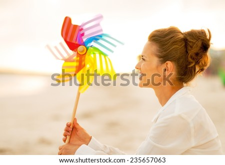 Happy young woman with colorful windmill toy sitting on beach at the evening - stock photo