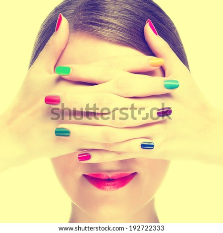 Happy young woman with colourful manicure. Toned image - stock photo