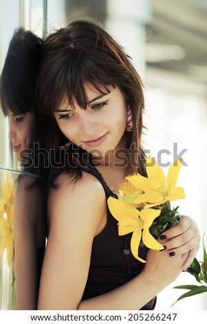 Happy young woman with flowers standing at the wall - stock photo