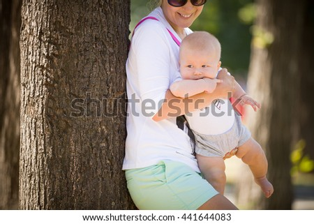 Happy young woman with her little infant baby having fun in the park. Mother with a child walking on sunny day. Mom and son outdoors. Woman holding adorable baby in her hands. - stock photo
