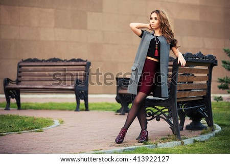 Happy young woman with long curly hairs walking on city street. Female fashion model in grey coat - stock photo