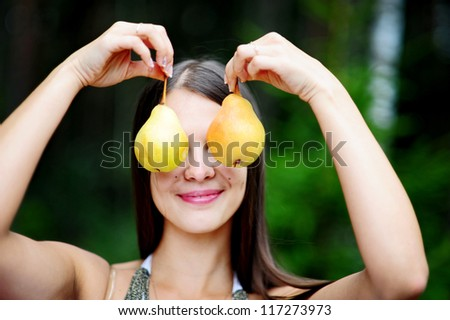 Happy young woman with pears in the form of earrings on picnic in park - stock photo