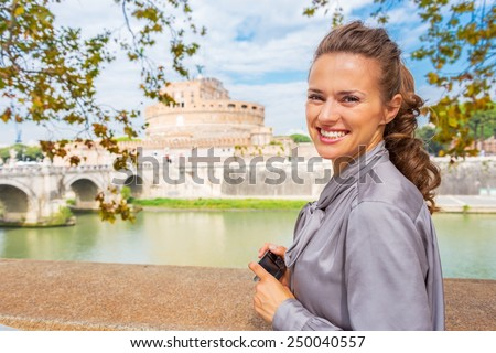 Happy young woman with photo camera standing on embankment near castel sant'angelo in rome italy - stock photo