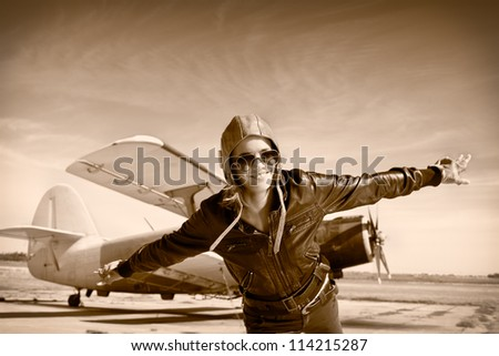 Happy young woman with raised hands  flying on airporte, Sepia photo. - stock photo