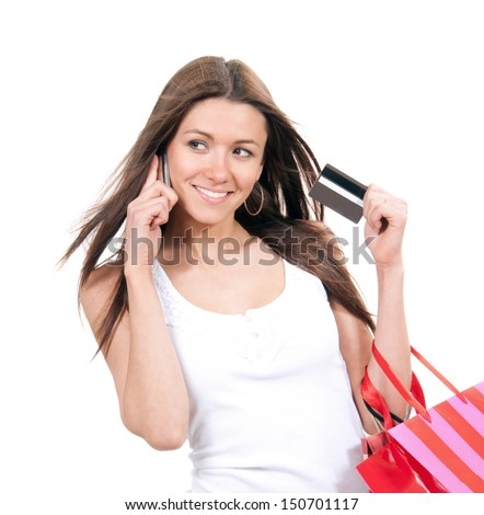 Happy young woman with shopping bags and credit card in hand talking on phone isolated on a white background - stock photo