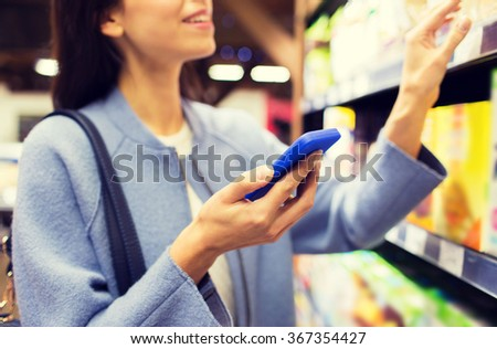 happy young woman with smartphone in market - stock photo