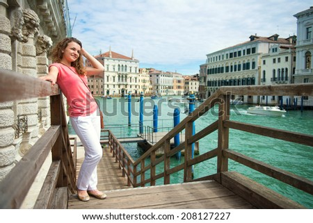 Happy young woman with tourist map in Venice - stock photo