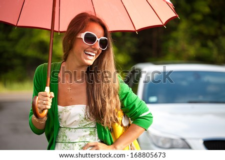 Happy young woman with umbrella under the summer rain. Girl enjoying rainy, smiling cheerful. - stock photo