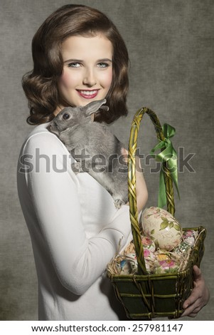 happy young woman with vintage hair-style posing in lovely easter portrait with fluffy rabbit and basket with some colorful eggs  - stock photo