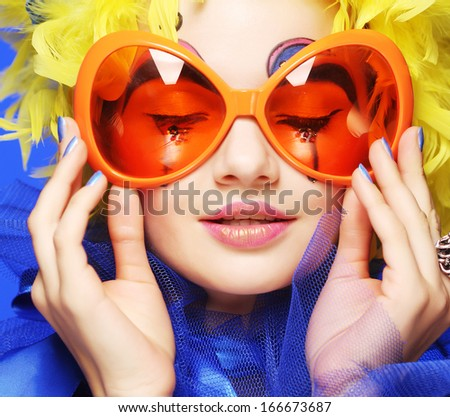 Happy young  woman with yellow  hair and carnaval glasses - stock photo