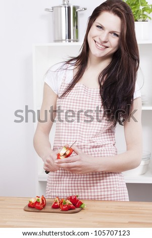 happy young woman working in the kitchen cutting paprika - stock photo