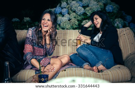 Happy young women couple friends laughing and drinking in a outdoors party. Friendship and celebrations concept. - stock photo