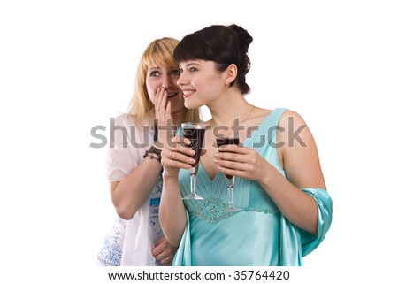 Happy young women friends talking and laughing.Girl in greenness of the sea dress is standing and holding wine glass. Woman in white dress is telling a secret to another. Isolated on white background. - stock photo
