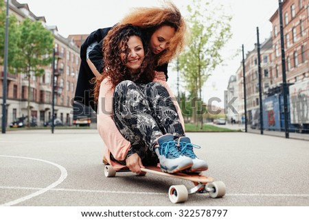 Happy young women having a lot of fun, riding together on skateboard. Women pushing her friend sitting on a long board - Outdoors - stock photo