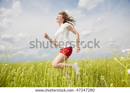 Happy young women runing in field - stock photo