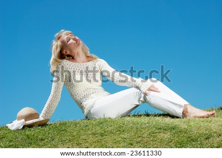 Happy young women sit in grass - stock photo