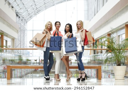 Happy young women with shopping bags posing in mall - stock photo