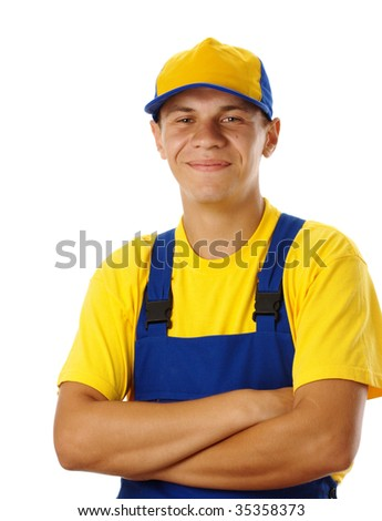 Happy young worker fold his arms, dressed in blue-and-yellow uniform and baseball hat, isolated over white - stock photo