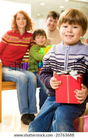 Happy youngster with Christmas present sitting on pink box and looking at camera - stock photo