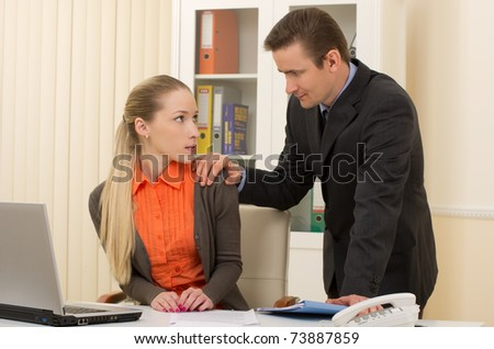 harass to his admin/office staffperson touching her shoulder - stock photo