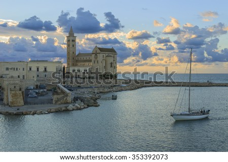Harbor at sunset:Trani cathedral(Apulia) -ITALY-It is a great example of Apulian Romanesque architecture.It was built using a calcareous tuff, characterised by its colour, an extremely light pink. - stock photo