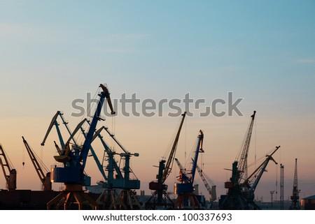 Harbor cranes on the sunset sky background - stock photo