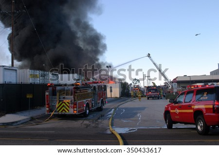 HARBOR GATEWAY, CALIFORNIA- DECEMBER 12, 2015: Fire erupts at recycling yard in Harbor Gateway. Dozens of Fire Trucks arrive to help extinguish an industrial fire, California Dec. 12, 2015   - stock photo