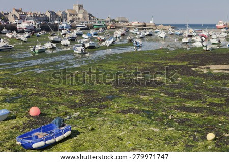 Harbor of Barfleur in Normandy at low tide - Barfleur, Basse Normandy, France - Focus is on the foreground not on the village - stock photo