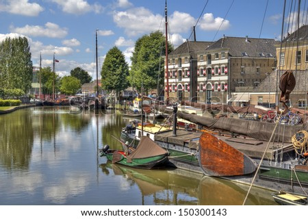 Harbor of Gouda, Holland, with historical warehouses and boats - stock photo