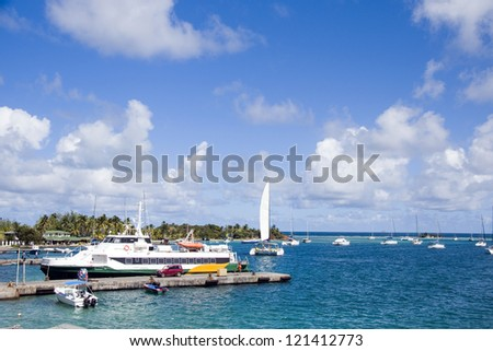 harbor port with jetty hotel passenger ferry and yacht sailboats Clifton Union Island St. Vincent and the Grenadines in Caribbean - stock photo